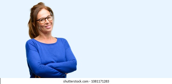 Middle age woman wearing wool sweater and glasses with crossed arms confident and happy with a big natural smile laughing isolated blue background