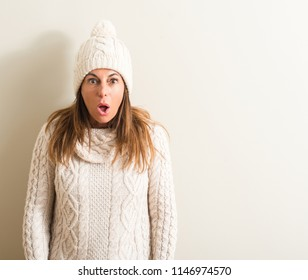 Middle age woman wearing wool winter cap scared in shock with a surprise face, afraid and excited with fear expression