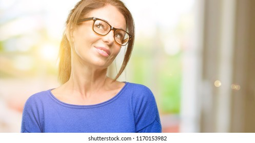 Middle age woman wearing wool sweater and glasses thinking and looking up expressing doubt and wonder