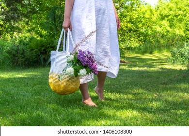 Middle age woman in white simple linen dress stays barefoot on the grass in beautiful garden and holds knitted white-yellow bag with flowers bouquet  inside, placeholder
