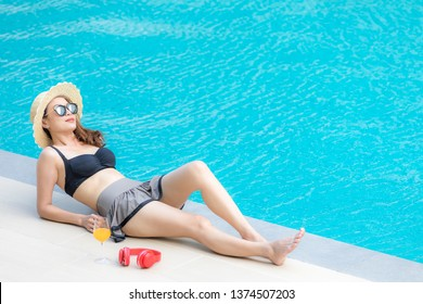 Middle aged 40 years old oman wear bikini lay beside blue water  swimming pool with  and looking to somewhere high point,  there are glass of orange and headphone beside her.