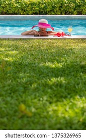 Middle aged 40 years old woman wear big hat and bikini standing in swimming pool in sunlight and using tablet computer. There are red headphone, sunglasses and glass of orange juice beside her.