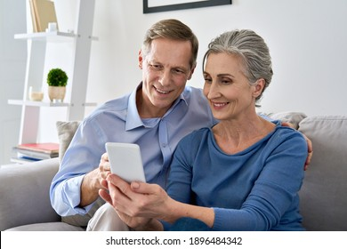 Middle aged 50s senior couple holding device looking at smartphone using mobile apps tech, shopping in ecommerce application, ordering delivery, buying goods online on cell phone sit on sofa at home.
