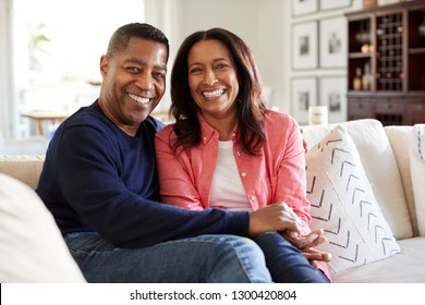 Middle aged African American couple sitting on the sofa in their living room looking to camera, front view, close up