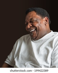 middle aged African American man laughing wearing a white t-shirt against a dark background