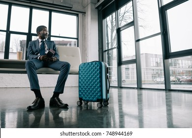 Middle aged African american man in suit waiting for a flight at the airport