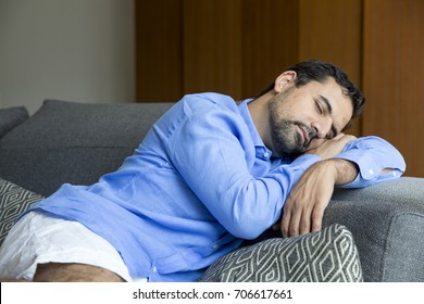 middle aged arab man resting on a sofa in his city apartment