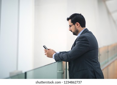 middle aged arab man texting on his phone