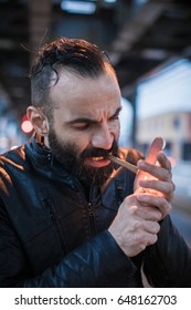 A middle aged, Arabic man lights a cigar in the streets of Brooklyn, New York City. Shot using ambient lighting during the sping of 2017.