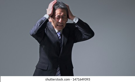 Middle aged asian businessman having a head ache. Brain stroke concept. Cerebral hemorrhage.