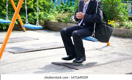Middle aged asian businessman riding on swing.