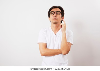 Middle aged Asian man with confused expression isolated on white background.