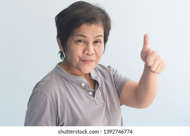 middle aged asian woman giving yes, ok, approving thumb up gesture
