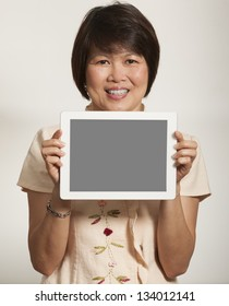 Middle aged Asian woman holding a computer tablet