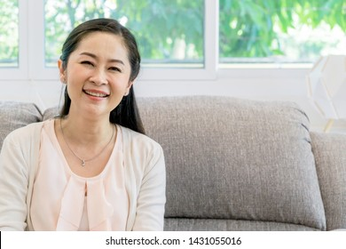 Middle aged Asian woman portrait sitting on a couch indoors.