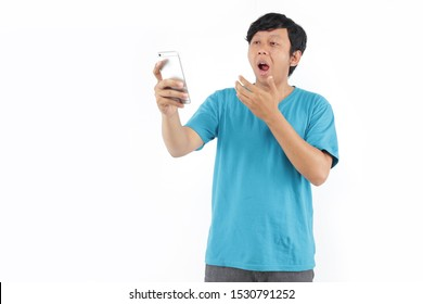 middle aged asians on phone surprised with blue t-shirt. business filipino surprised with smartphone