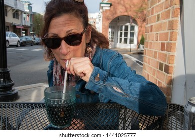 Middle aged baby boomer woman sitting at an outdoor restaurant table by a street sips soda through a straw from a fancy plastic glass. She is wearing sunglasses.