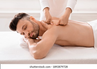 Middle aged bearded man attending modern male spa, laying on massage table, getting healing body procedure, enjoying his day at spa. Masseuse pressing on man back, using acupressure technique