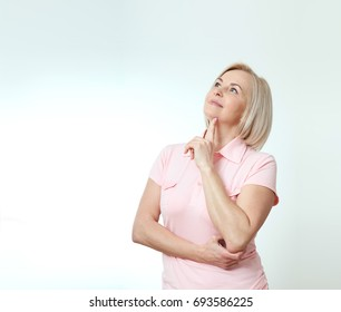 Middle aged beautiful woman looking up thinking and dreaming isolated on white background