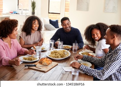 Middle aged black couple sitting at dinner table eating with their children, close up
