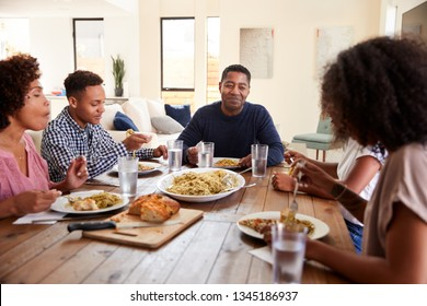 Middle aged black man sitting at the table eating dinner with his wife and family, close up