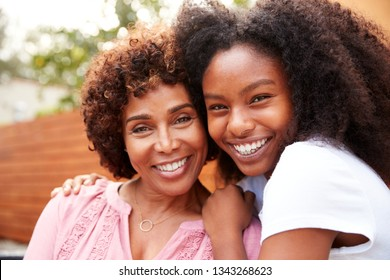Middle aged black mum and teenage daughter embracing and smiling to camera