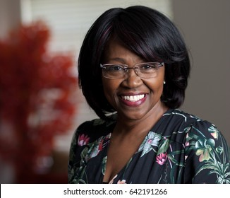 A middle aged black woman smiling