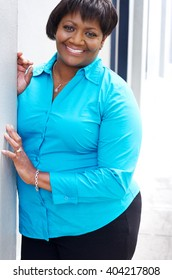 A middle aged black/african american woman smiling and happily leaning against a wall