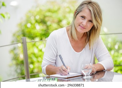 middle aged blond woman working at home without stress