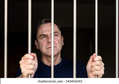 Middle aged blue eyed man incarcerated and wearing blue shirt stands holding prison bars