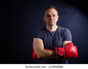 Middle aged boxer amateur trains on a dark background.