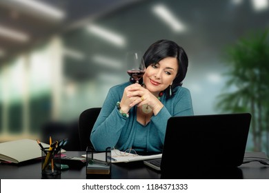 Middle aged brunette lady boss talks to someone nice on line. She holds a glass of red wine in to hands and silently smiles.She is exhausted after the hard working hours and quietly listens