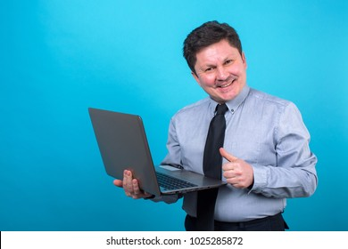 Middle aged business man with a laptop in hand on a blue background. Place for text.