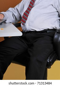 Middle aged business man sitting at his desk working. Man's poor posture and physical appearance along with seeing the butt of a cigarette may show bad lifestyle and could lead to physical problems.