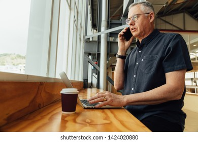 Middle aged business man working at high desk