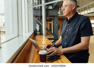 Middle aged business man working at high desk on laptop and looking out the window