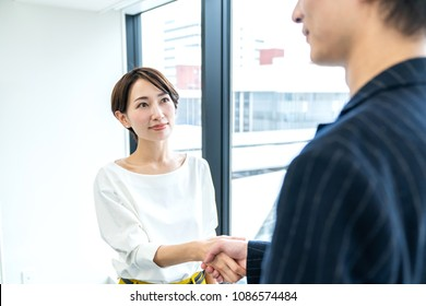 Middle aged business people shaking hands in the office.