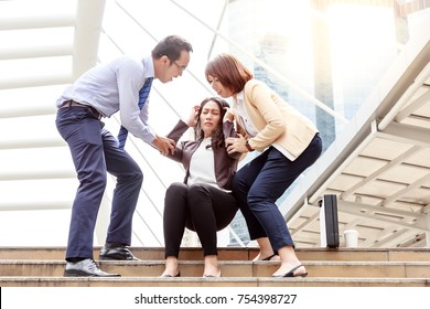 A middle aged business woman is fainted and fallen on floor. Her friends help her and their are shocking. The business woman gets stressed from her work. She faints at the city while goes to office.