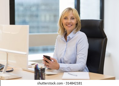 Middle aged business woman working at office. Using smartphone