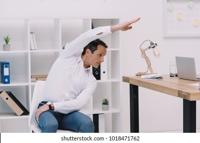 middle aged businessman doing side bend on chair at office