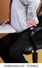 Middle aged businessman feeling pain in his back from unhealthy diet and poor seated posture while sitting at his work desk.