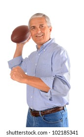 A middle aged businessman in jeans and dress shirt throwing an American football. Vertical format isolated over white.