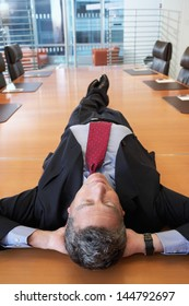 Middle aged businessman lying on conference table at office
