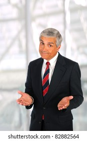Middle aged businessman in modern office setting making a gesture with both hands. Vertical Format.