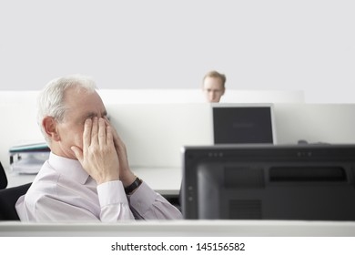 Middle aged businessman rubbing eyes at computer desk with colleague in background