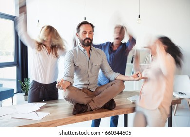 Middle aged businessman sitting on table and meditating in lotus position while colleagues running around