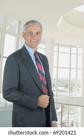 Middle aged businessman standing in modern office lobby. Vertical format with man smiling at the camera.