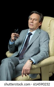 middle aged businessman in suit sitting on armchair isolated on black