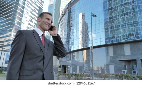 Middle Aged Businessman Talking on Phone, Standing Outside Office