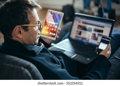 Middle aged businessman working from home multitasking comfortable in armchair